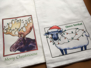 2 kitchen towels printed with designs Merry Christmoose and Fleece Navidad